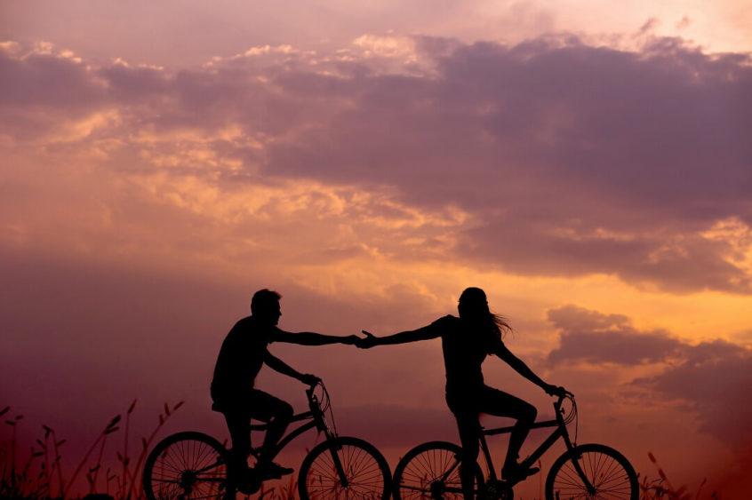 自転車に乗ってる男女カップルが手をつないでる所