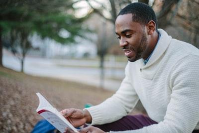 黒人が公園のベンチに座りながら本を読んでいるところ