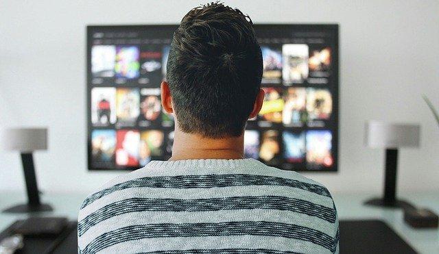 家で映画を観ている男の子の後ろ姿