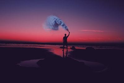 暗い夕焼けの中で男の人が煙を上げているところ