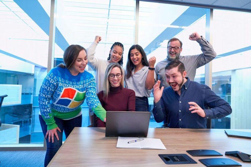 パソコンを見て6人の男女が喜んでいるところ